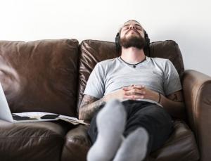 تصویر آقای که بعد از کار در حال استراحت است و به موزیک گوش می دهد